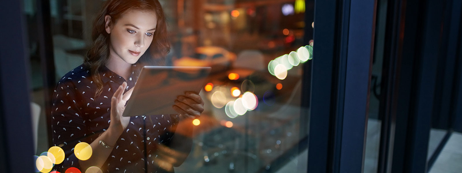 Woman standing by a window looking at an ipad