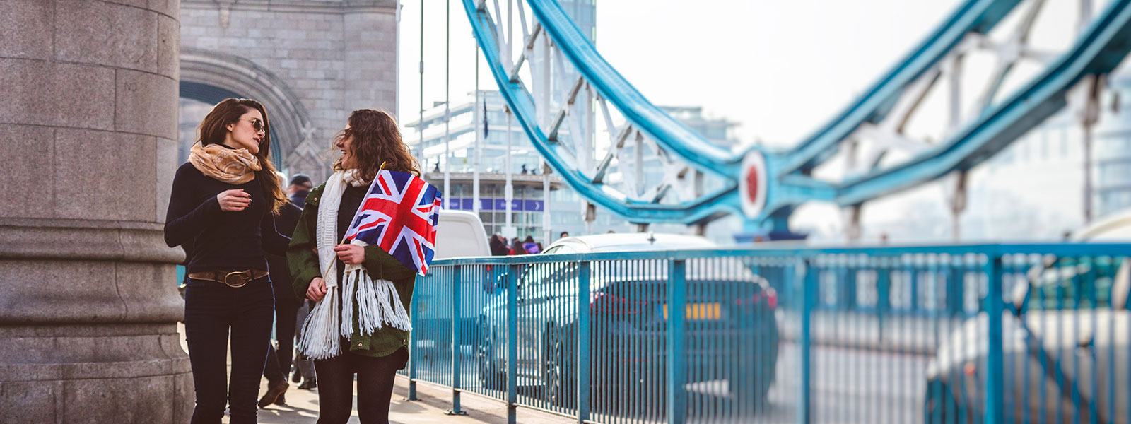 Two people walking holding UK flag
