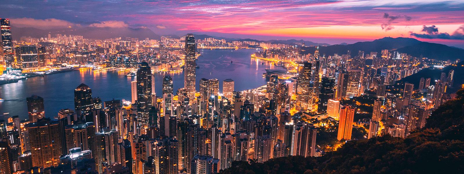 Hong Kong city high-rise buildings lit up at sunset
