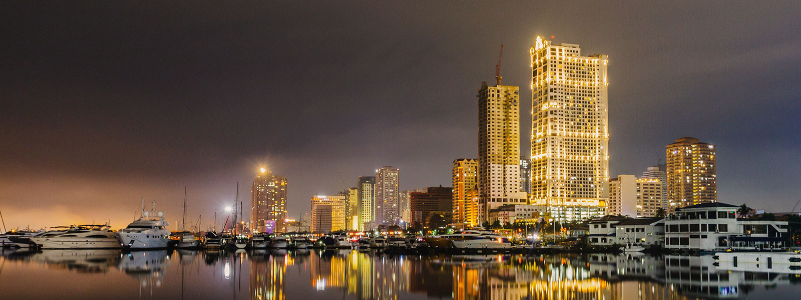 High-rise buildings lit up at night on a harbor shore