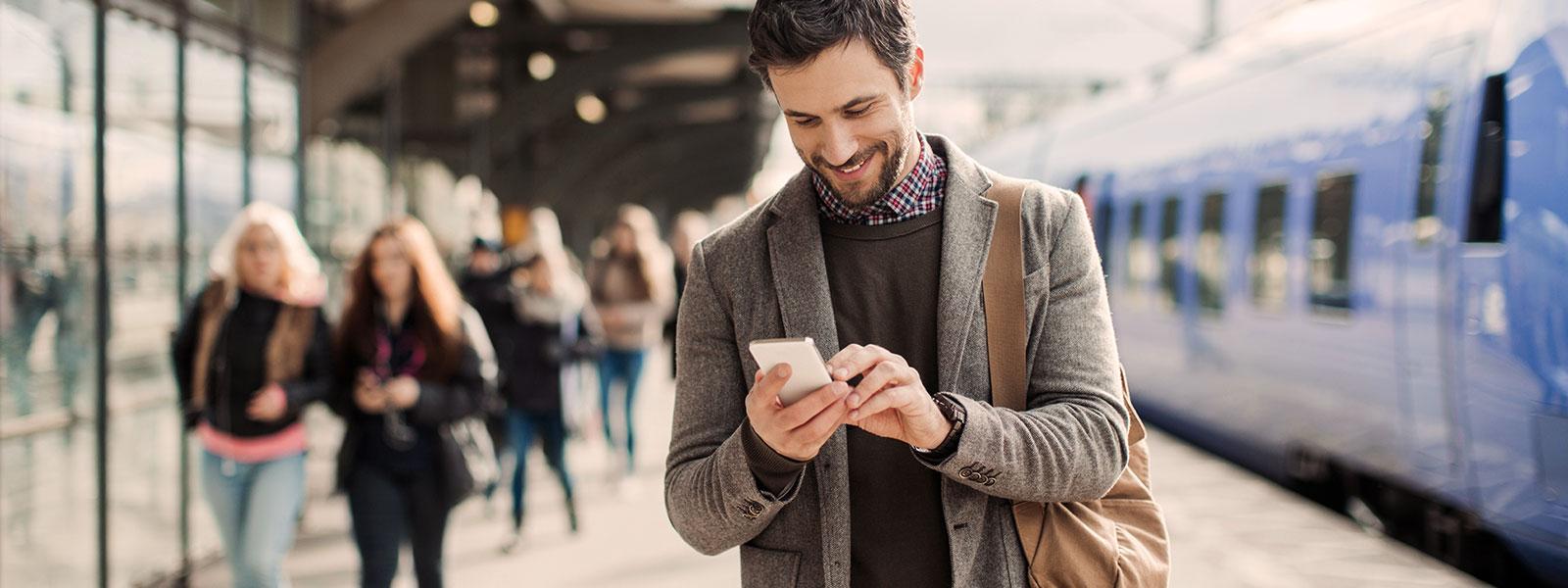 Man at a train platform smiling at his phone