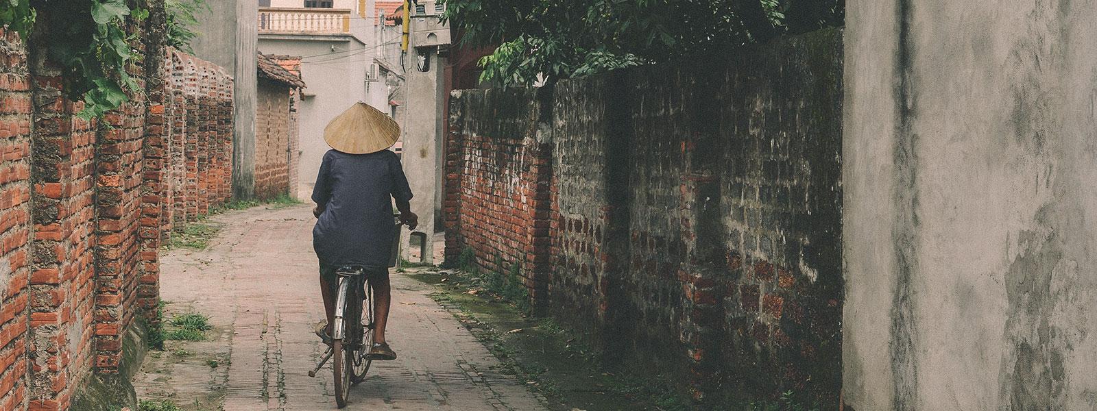 A person riding a bike through a quiet lane