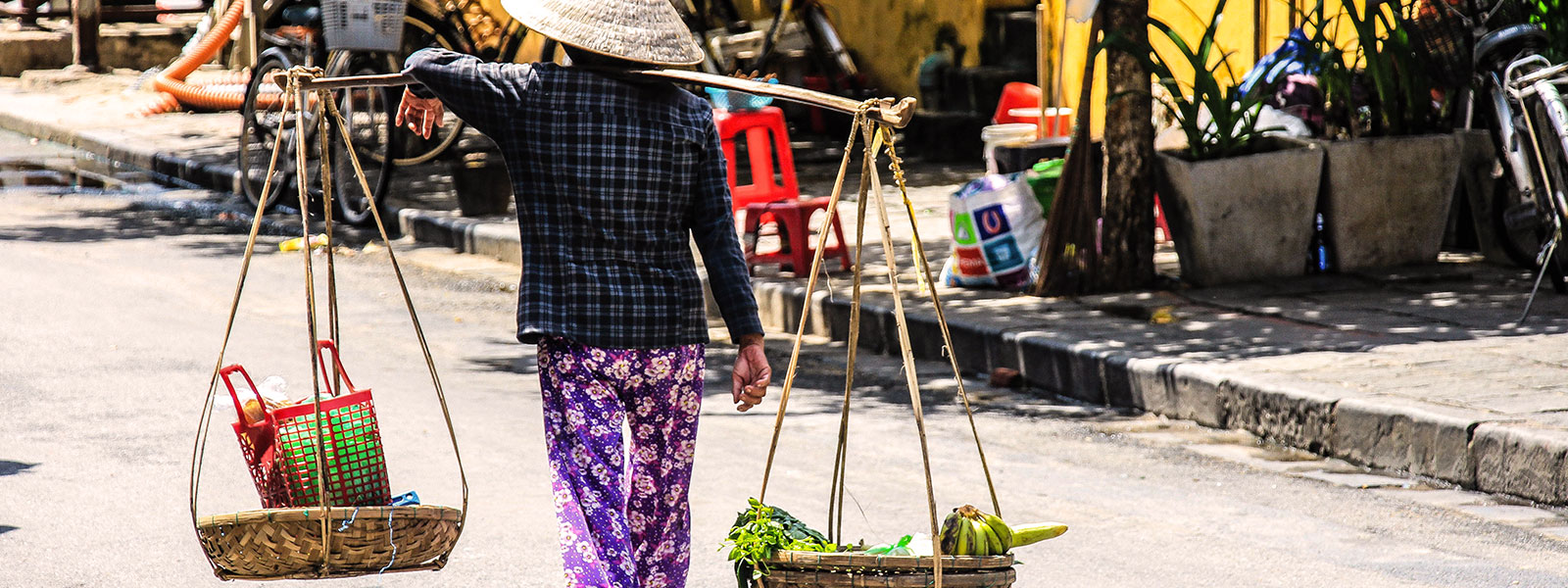 Local citizen carrying two baskets hanging from the shoulders on a busy street